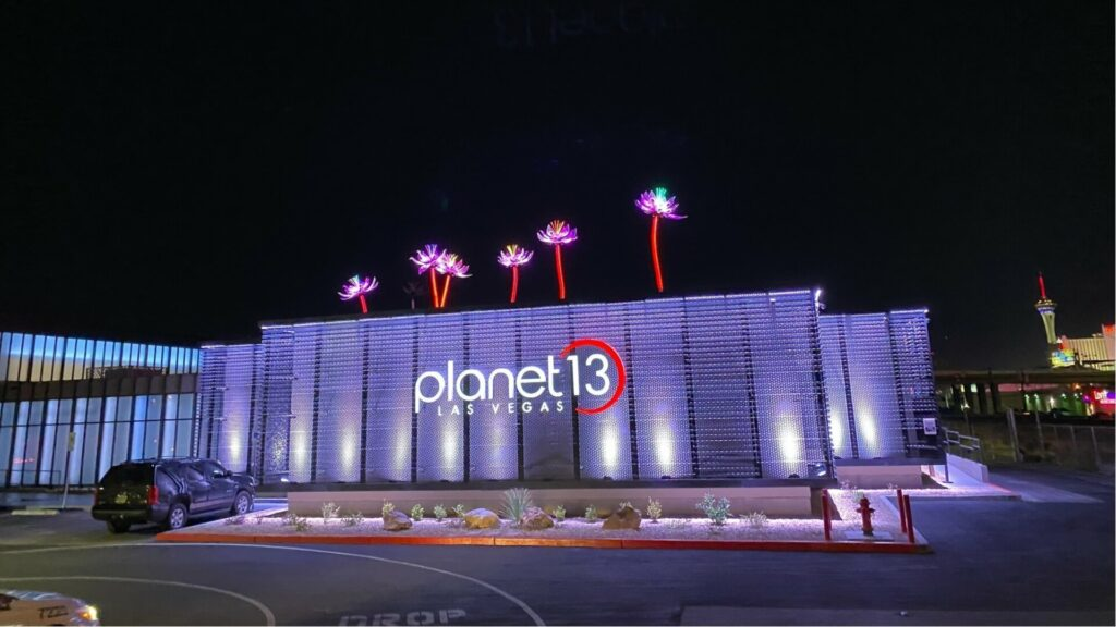 Lights shine on the facade of Planet 13