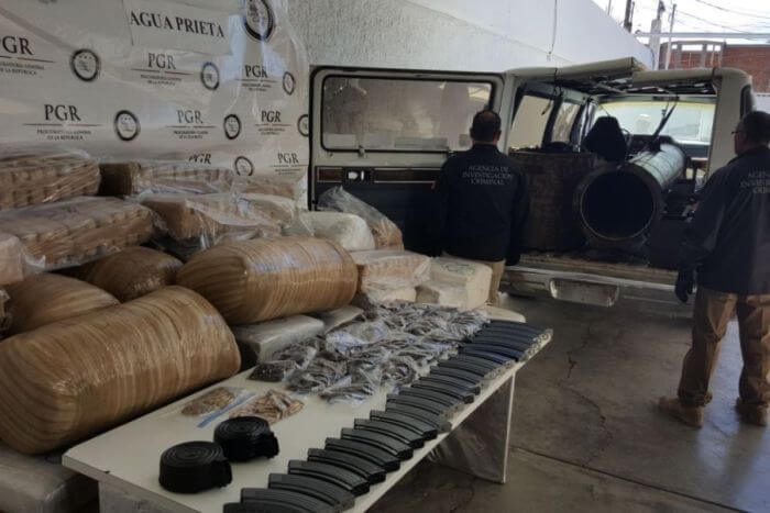 Packets of cannabis and ammunition magazines on a table with a marijuana cannon in the backgound