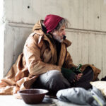 A homeless man sits on a streetcorner asking for donations