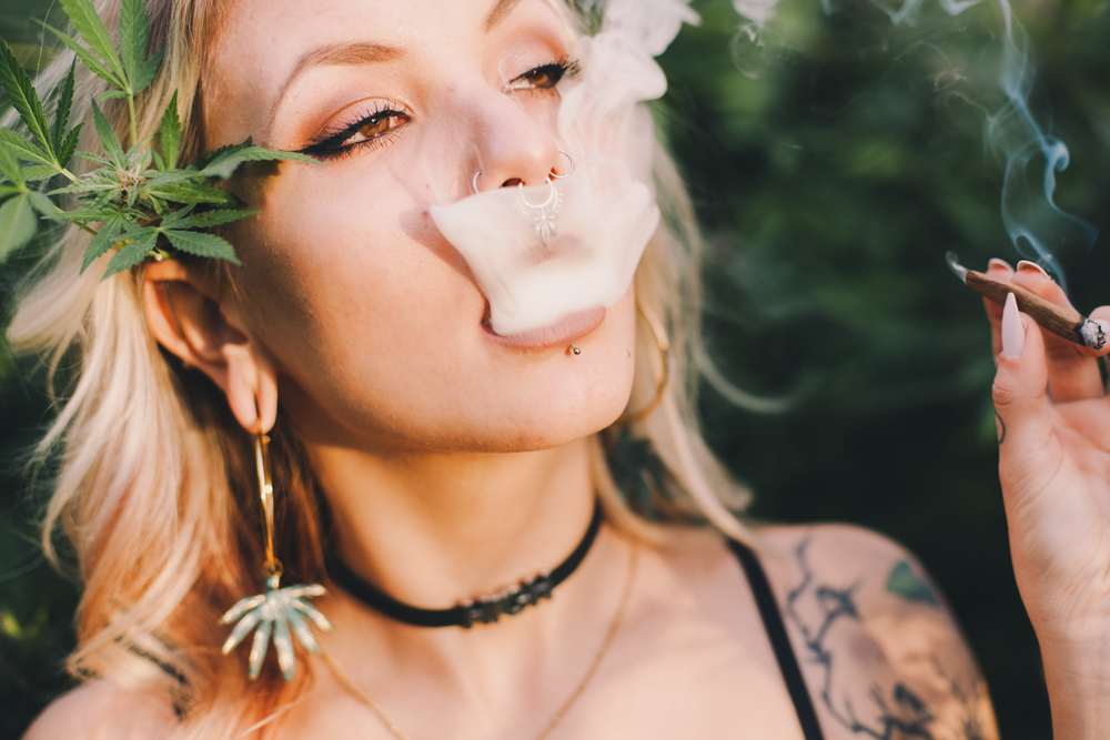 Young woman smoking a joint in a cannabis field