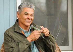 An older man smokes a marijuana pipe on his porch.